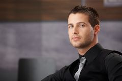 Young businessman sitting in modern office Stock Photo