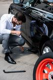 Young businessman sitting near broken car and using jack screw. At street stock photography
