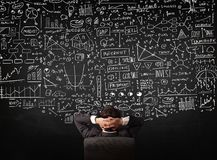 Businessman sitting in front of a blackboard with charts royalty free stock photos