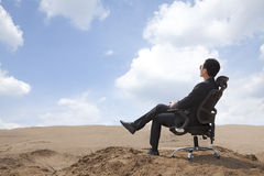 Young businessman sitting in an office chair in the middle of the desert Stock Photo