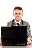 Young businessman sitting at office desk and looking at camera Royalty Free Stock Photography