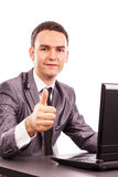 Young businessman sitting at office desk showing his thumb up Stock Image