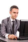 Young businessman sitting at office desk working with laptop Stock Photo