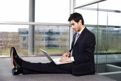 Young businessman sitting on office floor, typing on a laptop Stock Image