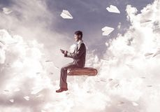 Businessman or student on book and paper planes flying around. Young businessman sitting on old book with mobile phone in hands Stock Photography