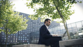 Young businessman sitting in a park near office and using laptop stock footage