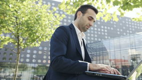 Young businessman sitting in a park near office and using laptop stock video