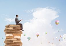 Man student reading book and aerostats flying around in air. Young businessman sitting on pile of books with one in hands Royalty Free Stock Photography