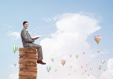Man student reading book and aerostats flying around in air. Young businessman sitting on pile of books with one in hands Stock Photography