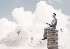 Man student reading book and aerostats flying around in air. Young businessman sitting on pile of books with one in hands Royalty Free Stock Images