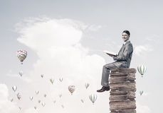 Man student reading book and aerostats flying around in air Royalty Free Stock Image