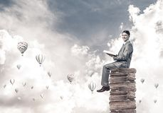 Man student reading book and aerostats flying around in air Stock Photos