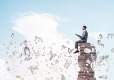 Man student on stack reading book and symbols flying around. Young businessman sitting on pile of books with one in hands Royalty Free Stock Images