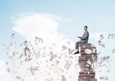 Man student on stack reading book and symbols flying around. Young businessman sitting on pile of books with one in hands Royalty Free Stock Image