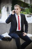 Young businessman sitting on platform while using cell phone Royalty Free Stock Photo