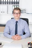 Young businessman is sitting relaxed at the desk Stock Photography