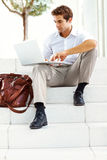 Young businessman sitting on steps and working Stock Image