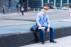 Young businessman sitting on the street near the business center Royalty Free Stock Photo