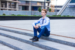 Young businessman sitting on the street near the business center Royalty Free Stock Photos