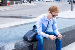 Young businessman sitting on the street near the business center and the works on the tablet Royalty Free Stock Photography