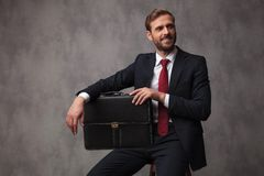 Young businessman sitting with a suitcase and looks to side royalty free stock image