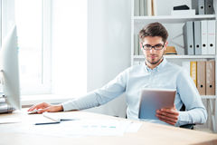 Young businessman sitting and using tablet computer in office Royalty Free Stock Photos