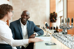 Young businessman sitting with woman at bar counter Stock Photography