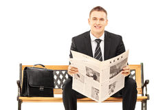 Young businessman sitting on a wooden bench with newspaper Stock Image