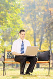 Young businessman sitting on a wooden bench and working on a lap Royalty Free Stock Photo