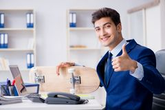 The young businessman with skate in office in sports concept. Young businessman with skate in office in sports concept Stock Images
