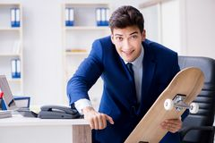 The young businessman with skate in office in sports concept. Young businessman with skate in office in sports concept Royalty Free Stock Image
