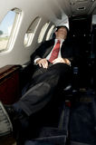 Young businessman sleeping in corporate jet. With feet up and chair back Stock Photo