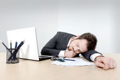 Young businessman sleeping on the office desk. Young tired businessman sleeping on the office  desk after long working hours, with documents, laptop and Royalty Free Stock Image