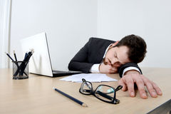 Young businessman sleeping on the office desk. Young tired businessman sleeping on the office  desk after long working hours, with documents, laptop and Royalty Free Stock Photos