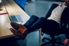Young businessman sleeping on table. Sleeping businessmans feet up on office table. Cropped picture of young mans feet with brown leather shoes on lying on Stock Photo