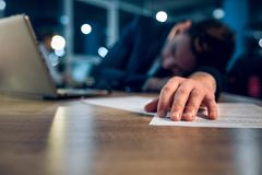 Young businessman sleeping on table. Close up photo of sleeping mans hand on wooden desk. Hand of overworked businessman who stayed up until late night in Royalty Free Stock Photos