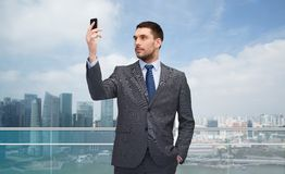 Young businessman with smartphone over city Stock Image
