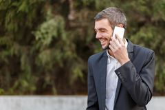 Young businessman with a smile talking on the phone on a blurry background of trees royalty free stock photos
