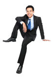 Young businessman smiling and looking at camera while sitting Stock Photos