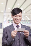 Young businessman smiling and looking down at airplane ticket at the airport, Beijing Royalty Free Stock Image