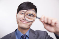 Young businessman smiling and looking through magnifying glass, studio shot Stock Photography