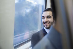 Young businessman smiling and looking out the window of the subway Stock Photo