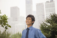 Young businessman smiling in the park, portrait Stock Photography