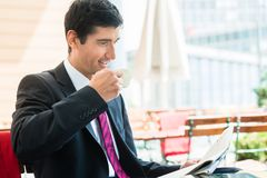 Businessman reading a newspaper and drinking coffee in the morni stock photo