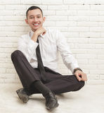 Young businessman smiling and sitting casually on the floor Royalty Free Stock Photography