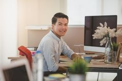 Young businessman smiling while sitting at his working place in office. Royalty Free Stock Photo
