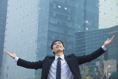 Young businessman smiling and standing outside with arms outstretched Royalty Free Stock Photo