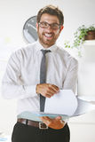Young businessman smiling and subject some papers in office. Royalty Free Stock Images