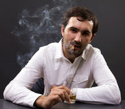 Young businessman smoking in his office Royalty Free Stock Photography