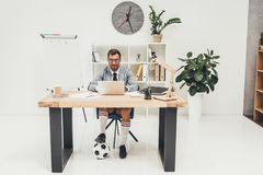 Young businessman in soccer shoes with ball under desk. At workplace Royalty Free Stock Photo